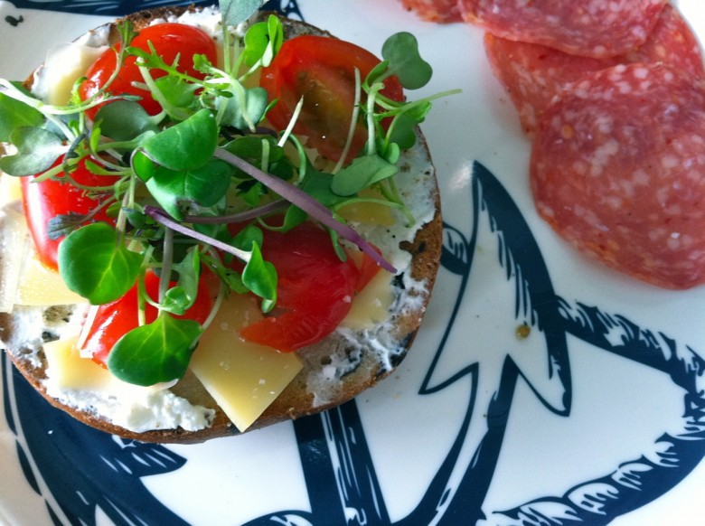 rosemary olive bagel with farm fresh goat cheese, guyere, tomato and spicy miro greens